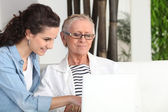 Younger and older woman sitting at a laptop — Stock Photo