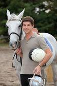 Teenage boy stood with horse — Stock Photo