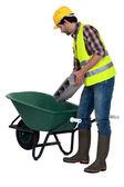 Werknemer een betonnen blok ingebruikneming een kruiwagen — Stockfoto