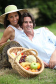 Couple posing with a fruit basket — Stock Photo