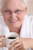 Portrait of an elderly woman drinking coffee — Stock Photo