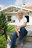 Elderly lady sat on decking — Stock Photo