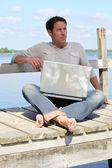 Mann am Laptop an einem See — Stockfoto