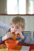 Little boy eating a croissant — Stock Photo