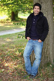 Young man near a tree in autumn — Stock Photo