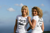Women wearing slogan t-shirts against a blue sky — Stok fotoğraf
