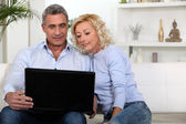 Couple sitting on sofa looking at laptop — Stock Photo