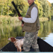 Hunter in a boat with a spaniel and a shotgun — Stock Photo