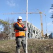 Tradesman holding a measuring stick - Stock Photo