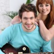 A man playing guitar and his girlfriend — Stock Photo #9220400