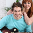 Stock Photo: A man playing guitar and his girlfriend