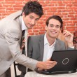 Handsome young men working at a laptop — ストック写真
