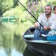 Couple fishing in a small boat on a river — Stock Photo