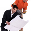 Electrician and architect looking at plans — Stock Photo