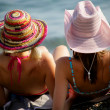 Two women sat on the in beach wearing hats — Stock Photo