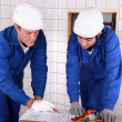 Stock Photo: Experienced tradesman teaching his apprentice how to read a blueprint