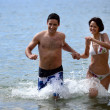 Couple running through water hand-in-hand — Stock Photo #9226943