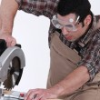Stock Photo: Carpenter with chainsaw