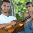 Man with acoustic guitar playing to girlfriend in park - Stockfoto