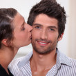 Woman kissing man on the cheek — Stock Photo