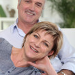 Middle-aged couple sat together on sofa — Stockfoto