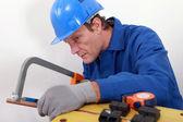 Industrial worker sawing copper pipe — Stok fotoğraf
