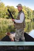 Hunter in a boat with a spaniel and a shotgun — Stockfoto