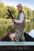 Cacciatore in una barca con uno spaniel e un fucile — Foto Stock