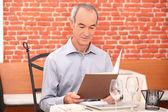 Man op zoek naar een menu in een restaurant — Stockfoto