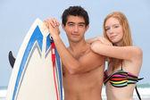 Ungt par på stranden med surfbräda — Stockfoto