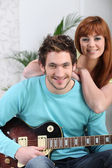 A man playing guitar and his girlfriend — Stock Photo