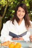 Vrouw lezen en ontbijten in de tuin — Stockfoto