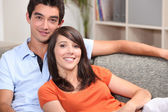 Young couple sitting on a sofa — Stock Photo