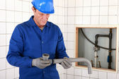 Artisan fitting two parts of pipe together — Stock Photo