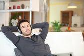 Man ontspannen met muziek op sofa — Stockfoto