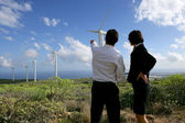 Business couple standing in a field of wind turbines — Stock Photo