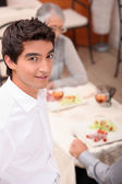 Young waiter serving lunch — Stock Photo