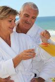 Pareja tomando un vaso de jugo por la orilla del mar — Foto de Stock
