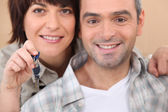 Mature couple holding up a set of keys — Stock Photo