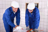 Experienced tradesman teaching his apprentice how to read a blueprint — Stock Photo