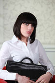 Woman sitting in a chair with a briefcase — Stock Photo