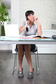 Ditzy secretary on the phone in her slippers — Stock Photo