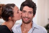 Woman kissing man on the cheek — Stock Photo