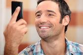 Man looking at phone smiling — Stock Photo