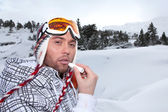 Portrait of a skier applying lip balm — Stock Photo