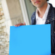 Man stood outside house with blue poster — Stock Photo