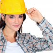 Female builder touching hat — Stock Photo