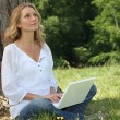 Blond woman sat by tree with laptop deep in thought — Stock Photo
