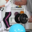 Stock Photo: Older couple working out in gym