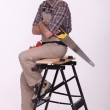 Laborer with saw sitting on a workbench — Stock Photo